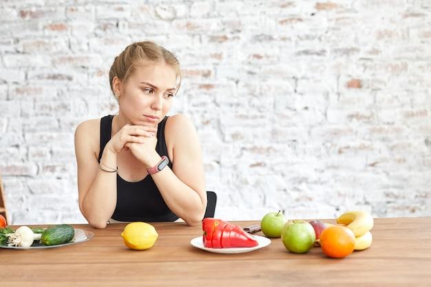 悲しい少女はテーブルの上に横たわっている野菜を見ます。ダイエットの習慣が変わります。悲しい女性は菜食を嫌います。