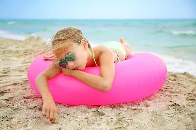 ピンクの膨脹可能な円の上に横たわっている悲しい少女。