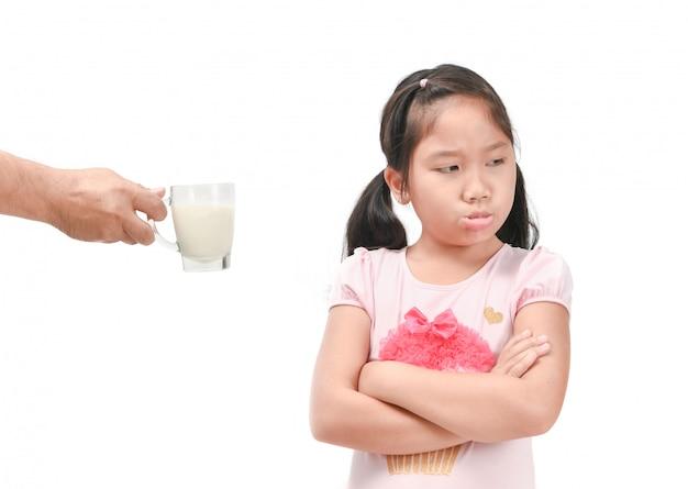 Sad girl refuses drink a fresh milk isolated