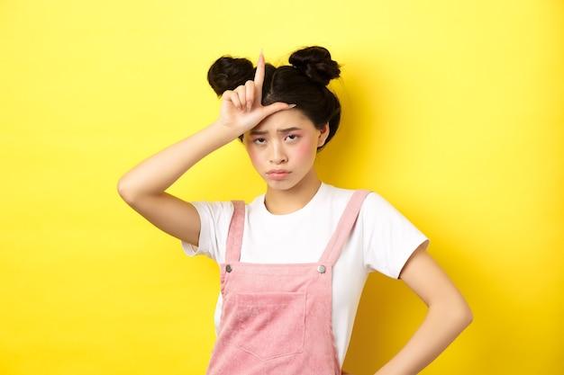 額に敗者のサインを見せ、動揺し、自分自身に失望し、黄色の上に立っている悲しい少女。