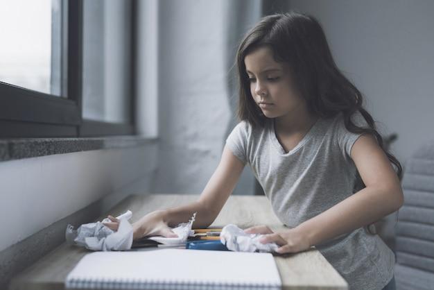 Грустная девушка сидит за столом с домашним заданием.