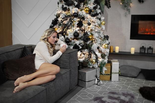 크리스마스 이브에 집에 혼자 앉아 있는 슬픈 소녀 차나 mulled 와인을 마시는 불행한 여자