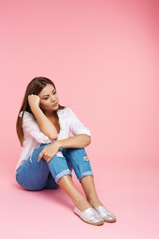 Sad girl sitting on floor looking down isolated on pink