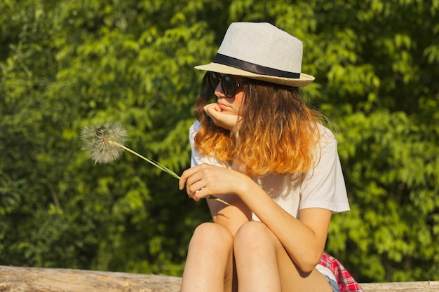 Sad girl sitting in nature with a fluffy dandelion, serious unhappy teenager