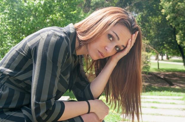 Грустная девушка сидит на скамейке в парке