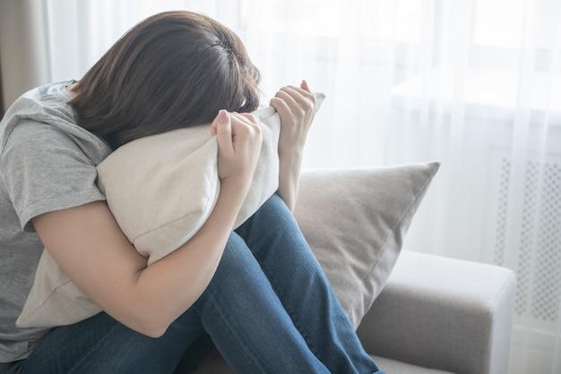 ソファに座って、枕、孤独、悲しみの概念を抱いて悲しい少女