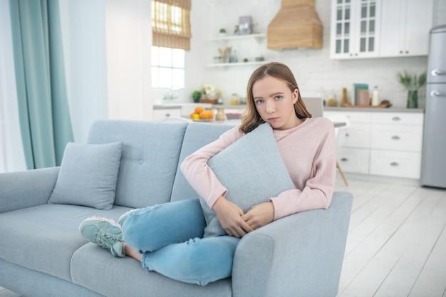 Грустная девушка сидит на диване, поджав под себя ноги, сжимая подушку, глядя перед собой.