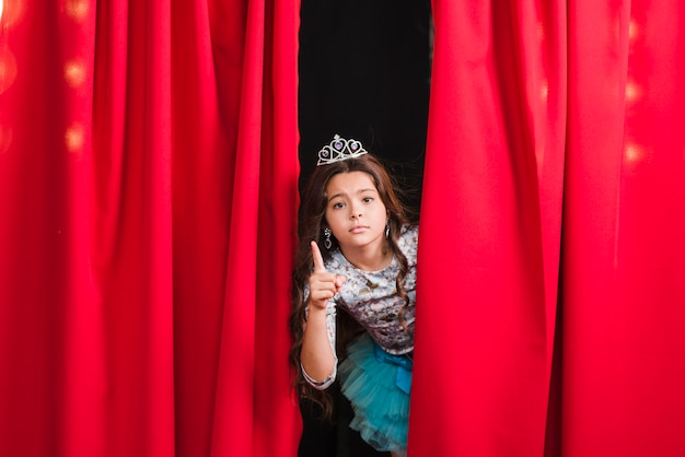 Sad girl standing behind the red curtain gesturing
