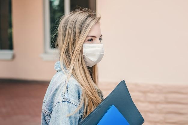 医療用防護マスクを身に着けている悲しい少女は大学、大学の建物に入り、フォルダーとノートを手に持っています