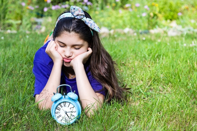 Sad girl with alarm clock in summer