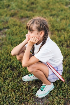 Sad girl with badminton crouching on green grass