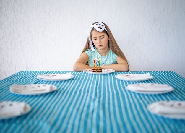 A sad girl with a cake with candles sits alone at a large table. loneliness concept.