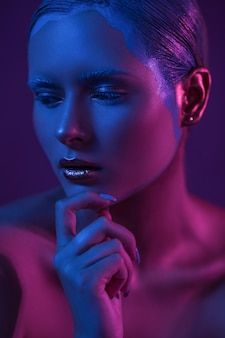 Sad girl with creative make up in blue and purple lights of neon