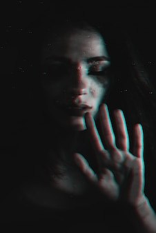 Sad girl with flowing mascara with glitch effect through the glass with raindrops