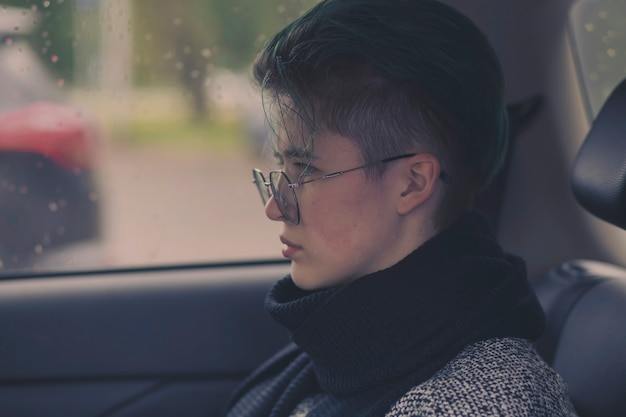 Sad girl with glasses sits in a car in autumn on a rainy day.