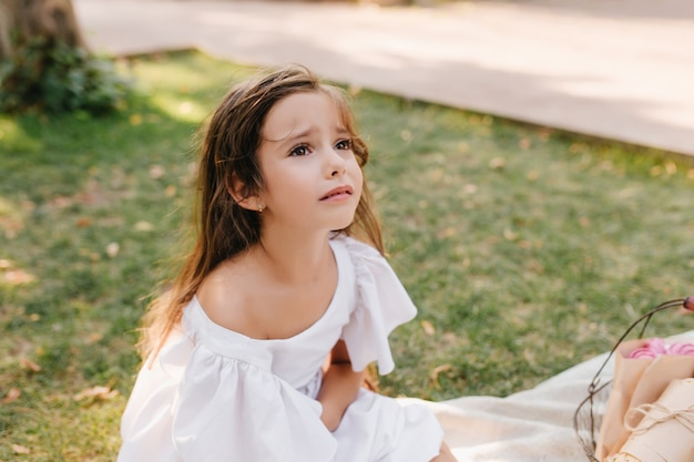 Sad girl with light-brown hair is about to cry sitting on blanket beside alley. outdoor portrait of unhappy child looking up with eyes full of tears in park.