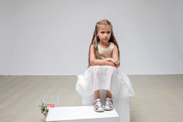 축제 드레스를 입은 긴 머리를 한 슬픈 소녀는 정사각형 연단 흰색 배경 스튜디오 샷에 앉아 있습니다