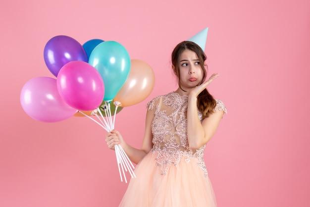 핑크에 풍선을 들고 파티 모자와 슬픈 소녀
