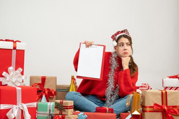 白のプレゼントの周りに座っているファイルを保持しているサンタの帽子を持つ悲しい少女