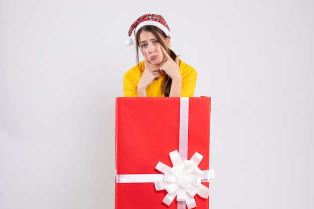화이트에 큰 크리스마스 선물 뒤에 산타 모자 서 슬픈 소녀