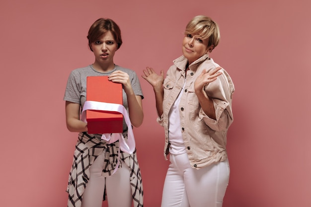 Sad girl with short hairstyle in modern clothes holding opened gift box and posing with blonde old woman in white outfit on pink background.