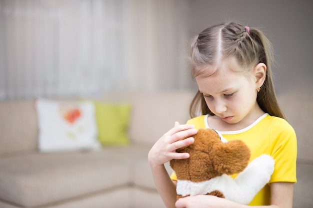 Sad girl with a toy dog at home