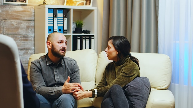 Sad girlfriend holding husband hands sitting on couch at couple therapy. therapist giving guidance to stressed couple.