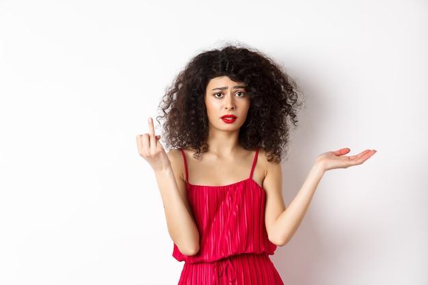 곱슬 머리를 가진 슬픈 여자 친구, 반지없이 손가락을 보이고 혼란스러워 보이며 우유부단 한 남자 친구에게 불평하고 결혼하고 싶어하며 흰색 배경에 서 있습니다.
