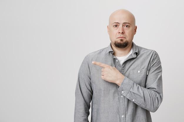 Sad gloomy bald man with beard pointing finger left