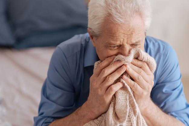 Sad gloomy elderly man burying his face in his deceased wife knitted jacket and crying while grieving about her