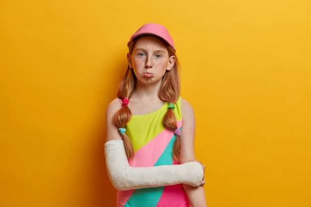 Sad gloomy freckled girl wears colorful bathing suit and cap, has broken arm in cast, spoiled vacation because of trauma, isolated over yellow wall. summer time, children, accident concept