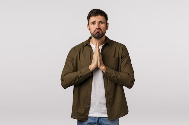 Sad, gloomy and miserable, depressed young man need help, begging for forgiveness, apologizing, press palms together in pray, supplicationg, frowning and pulling grimace, white background