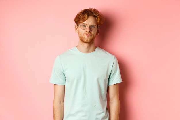 Sad and gloomy redhead bearded man in t-shirt and glasses, staring at camera bored and unamused, standing over pink background.