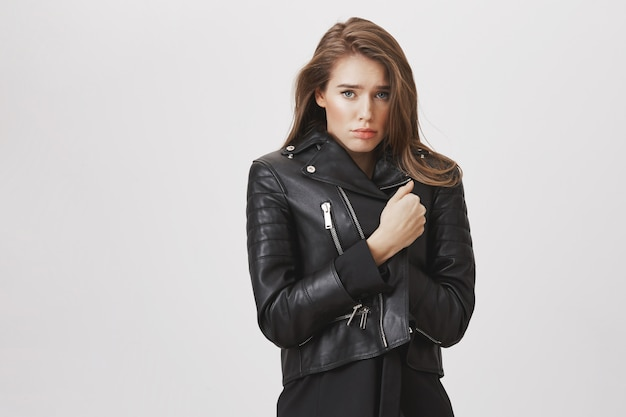 革のジャケットで寒さを感じて悲しい悲観的な女性