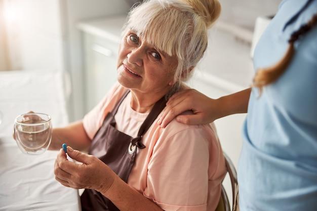 집에서 감기약을 먹고 있는 슬픈 할머니