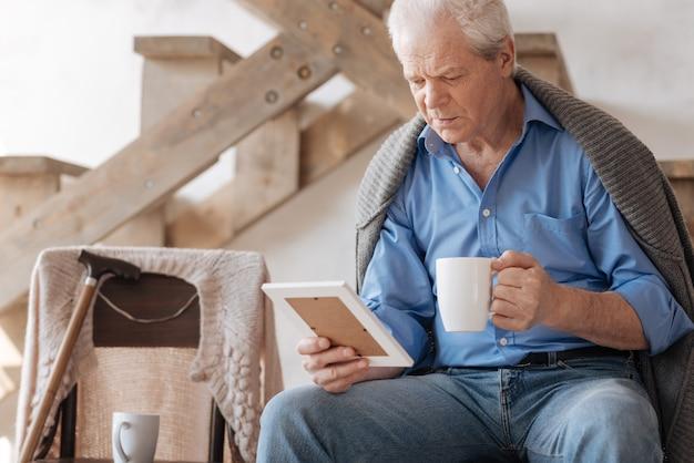 Грустный седой пожилой мужчина сидит на стуле и пьет чай, глядя на фотографию своей жены