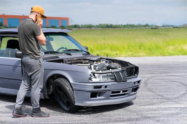 슬픈 남자 좌절 젊은 남자 드라이버는 도로 충돌 후 그의 부서진 충돌 자동차 근처에 서있다