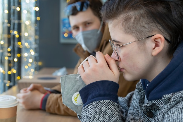 Sad guy and girl communicate while sitting in a cafe during a pandemic in protective face masks