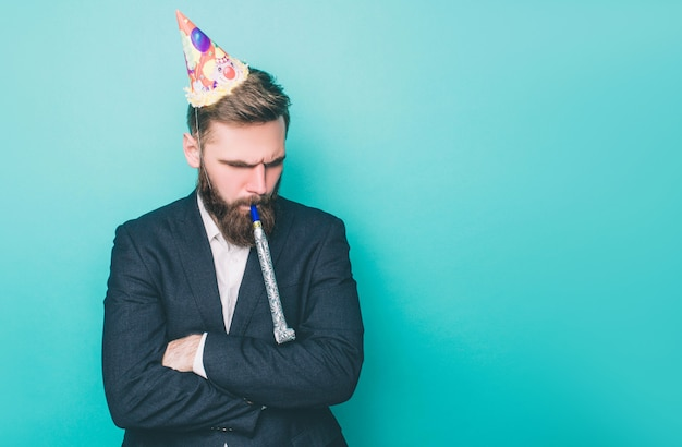 Sad guy is standing and looking down wearing a party hat