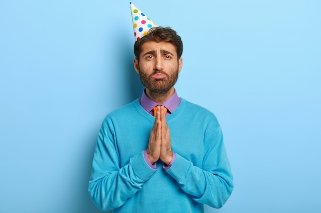 Sad guy with birthday hat posing in blue sweater