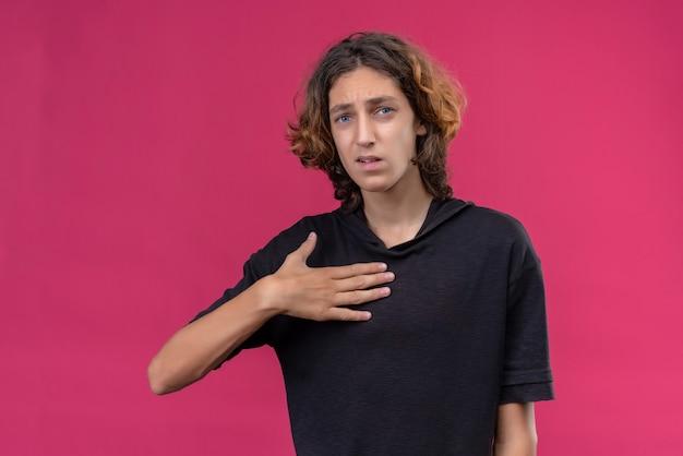 Ragazzo triste con i capelli lunghi in maglietta nera mise la mano sul petto sul muro rosa