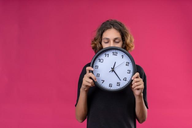 ピンクの壁に壁時計を保持している黒いtシャツの長い髪の悲しい男