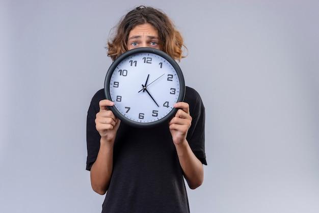 白い壁に壁時計を保持している黒いtシャツの長い髪の悲しい男