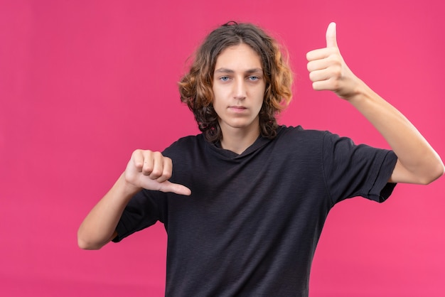 ピンクの壁に片方の手で親指を下に向けて親指を上に見せている黒いtシャツの長い髪の悲しい男