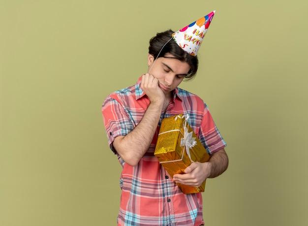 Sad handsome caucasian man wearing birthday cap puts hand on chin and holds gift box