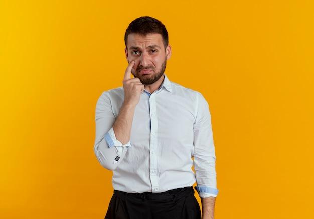 悲しいハンサムな男はオレンジ色の壁に隔離された目を指しています