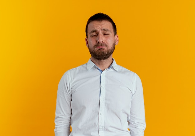 Triste bell'uomo sta con gli occhi chiusi isolati sulla parete arancione