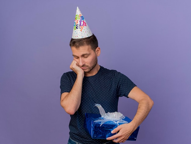 Sad handsome man wearing birthday cap puts hand on chin and holds gift box isolated on purple wall with copy space