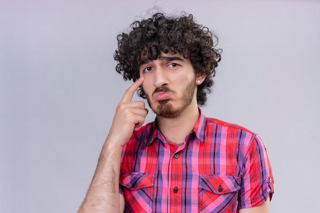 Un bell'uomo triste con i capelli ricci in camicia a quadri che punta con il dito indice sulla guancia