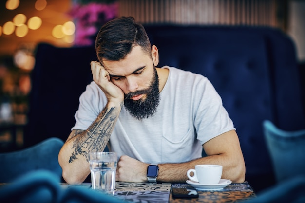 Sad handsome sad bearded caucasian hipster leaning on table while sitting in cafe. he is lost in his own thoughts.
